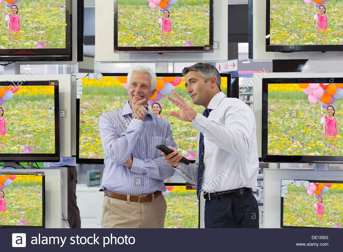 Flat screen televisions behind salesman and senior man in electronics store - Stock Image