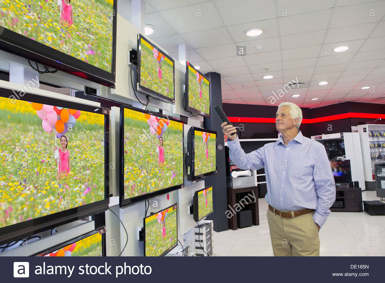 Senior man looking at flat screen televisions in electronics store - Stock Image