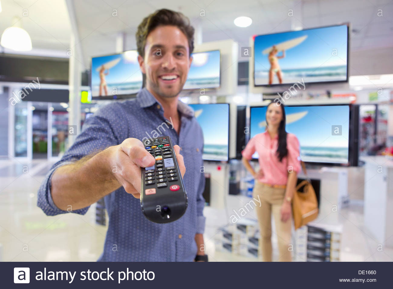 Portrait of smiling man holding remote control in front of televisions in electronics store - Stock Image