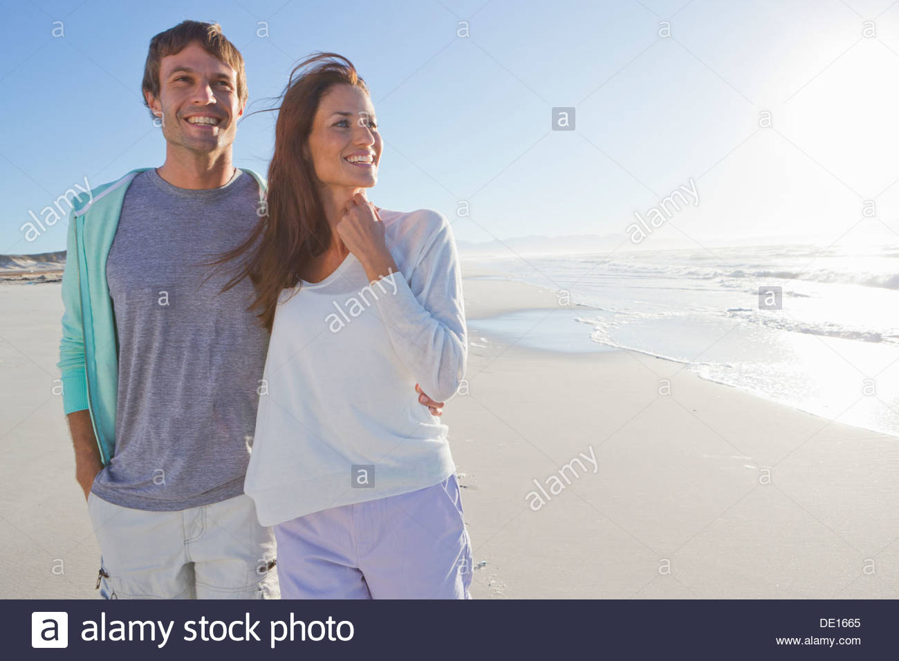 Happy couple on sunny beach - Stock Image