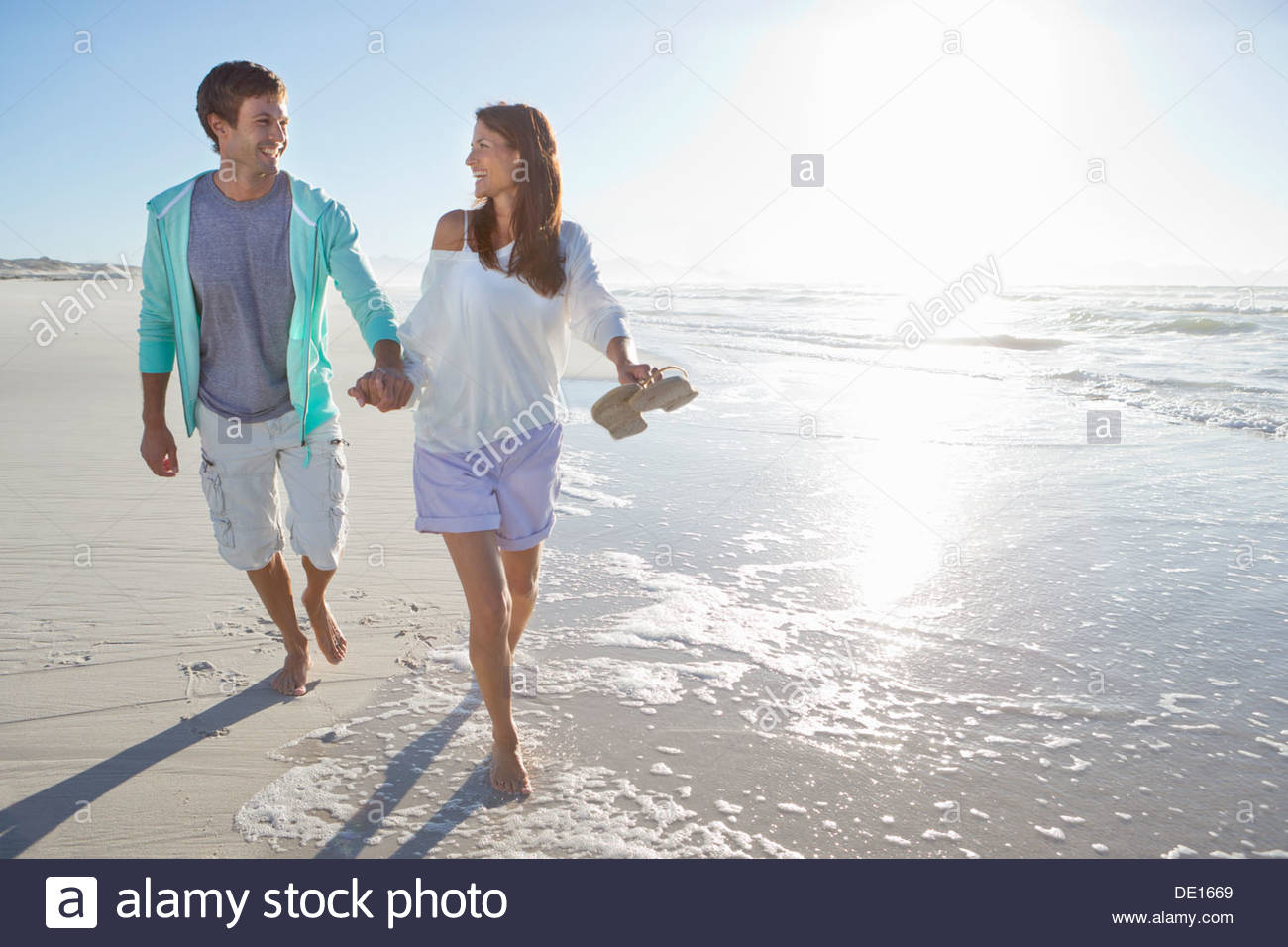 Happy couple holding hands and walking barefoot on sunny beach - Stock Image