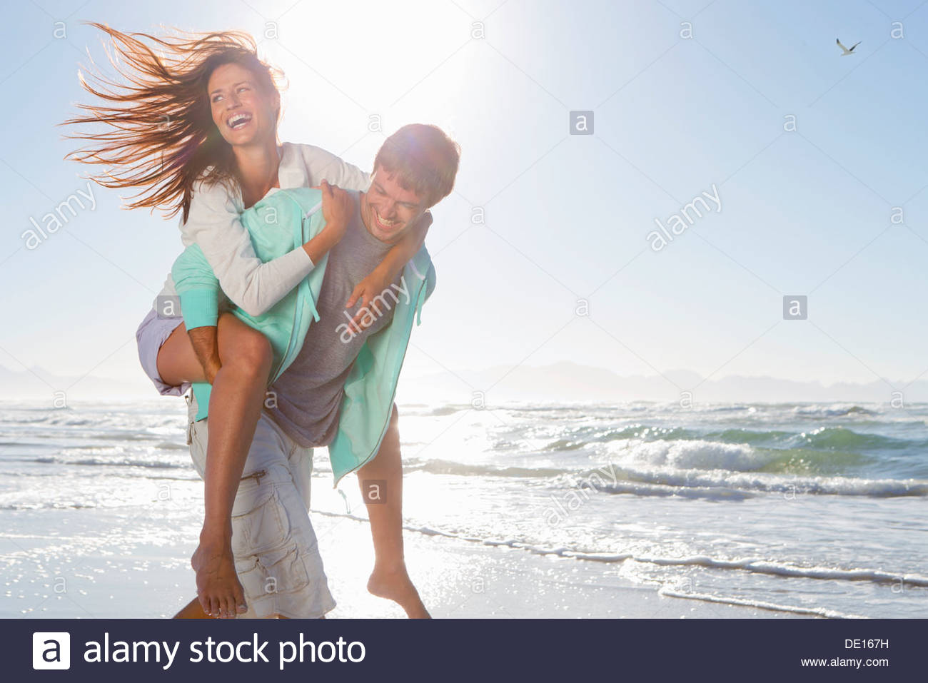 Man piggybacking enthusiastic woman on sunny beach - Stock Image