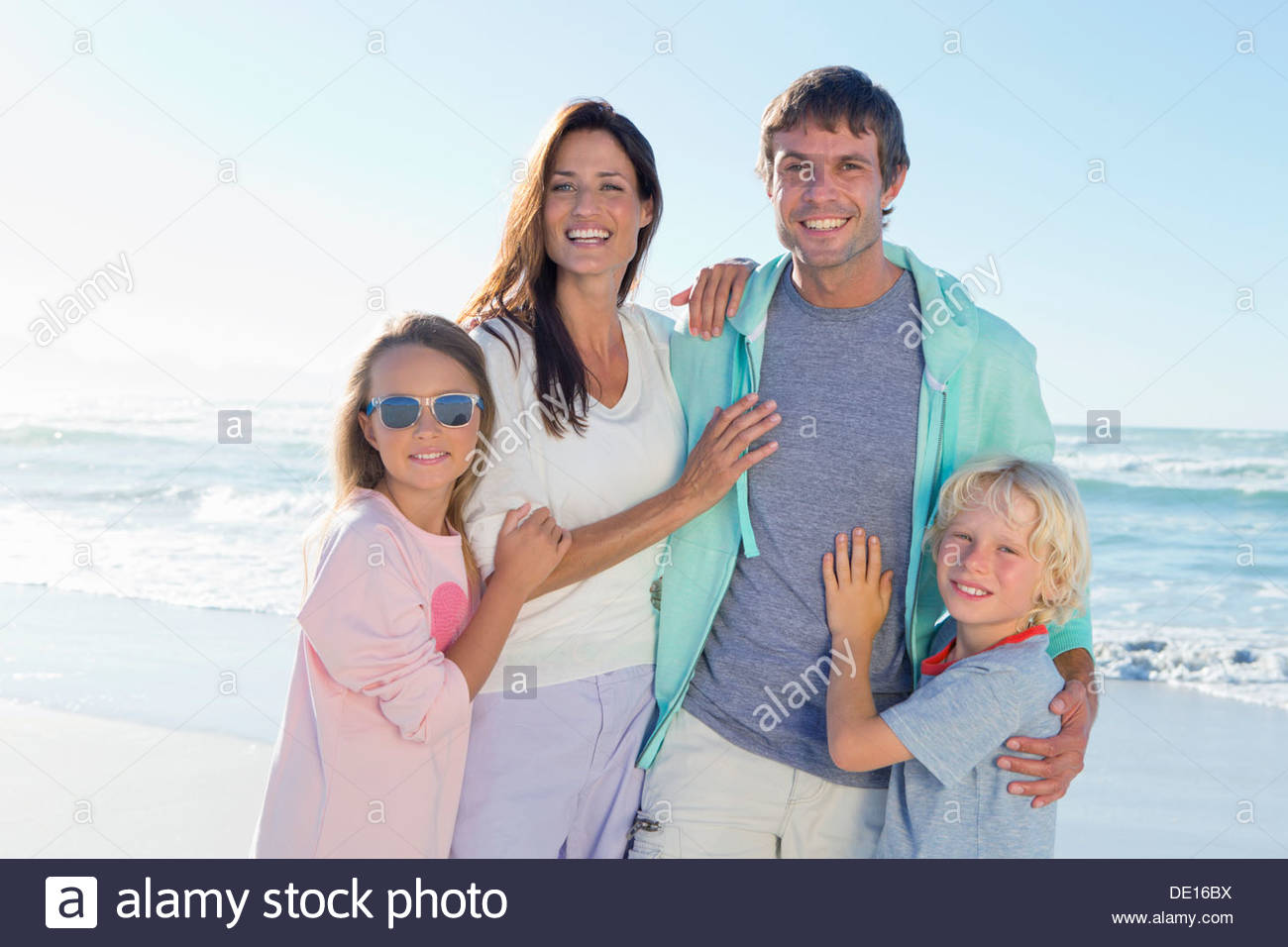 Portrait of happy family on sunny beach - Stock Image