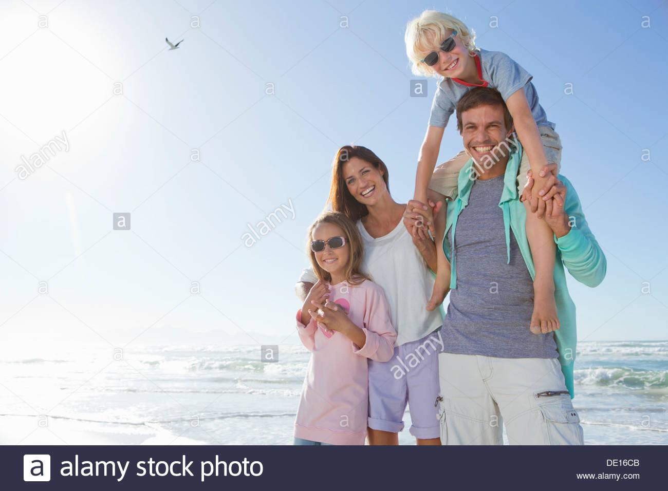 Portrait of happy family on sunny beach - Stock Image