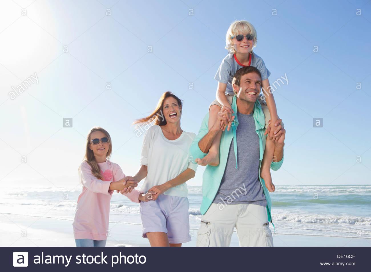 Happy family on sunny beach - Stock Image