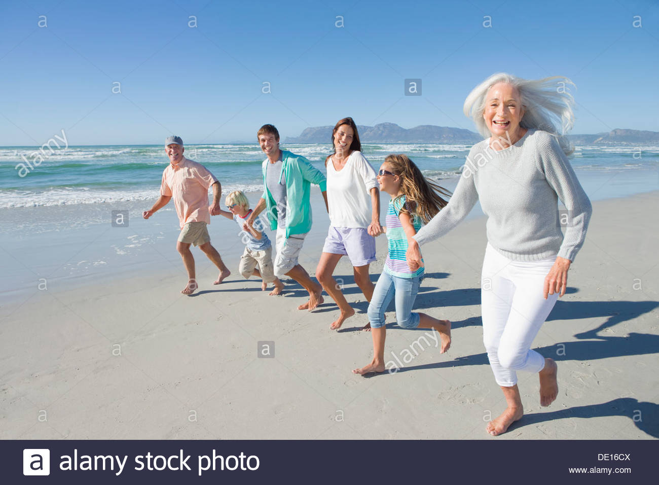 Portrait of happy multi-generation family holding hands and running on sunny beach - Stock Image