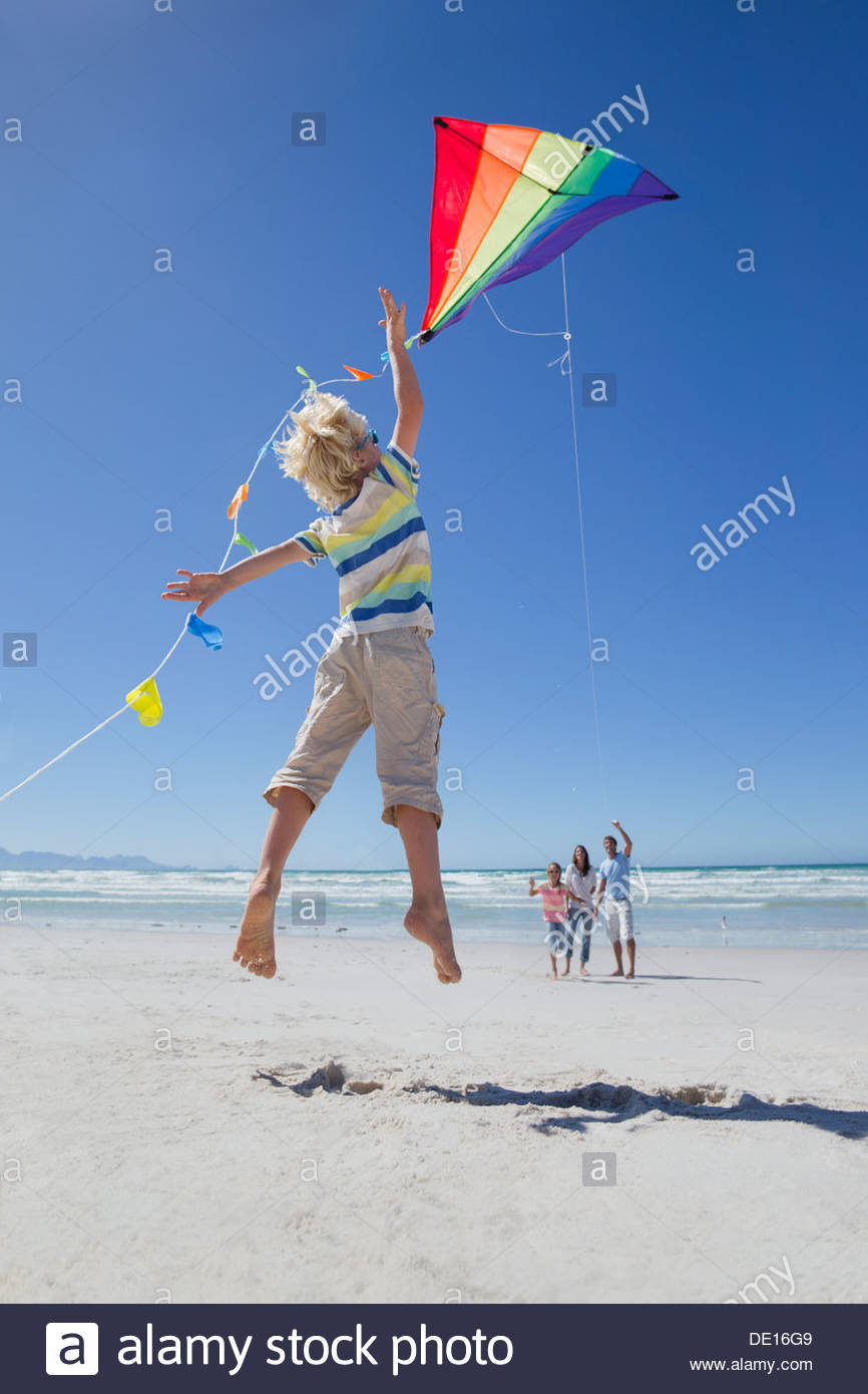 Boy jumping and reaching for kite on sunny beach - Stock Image