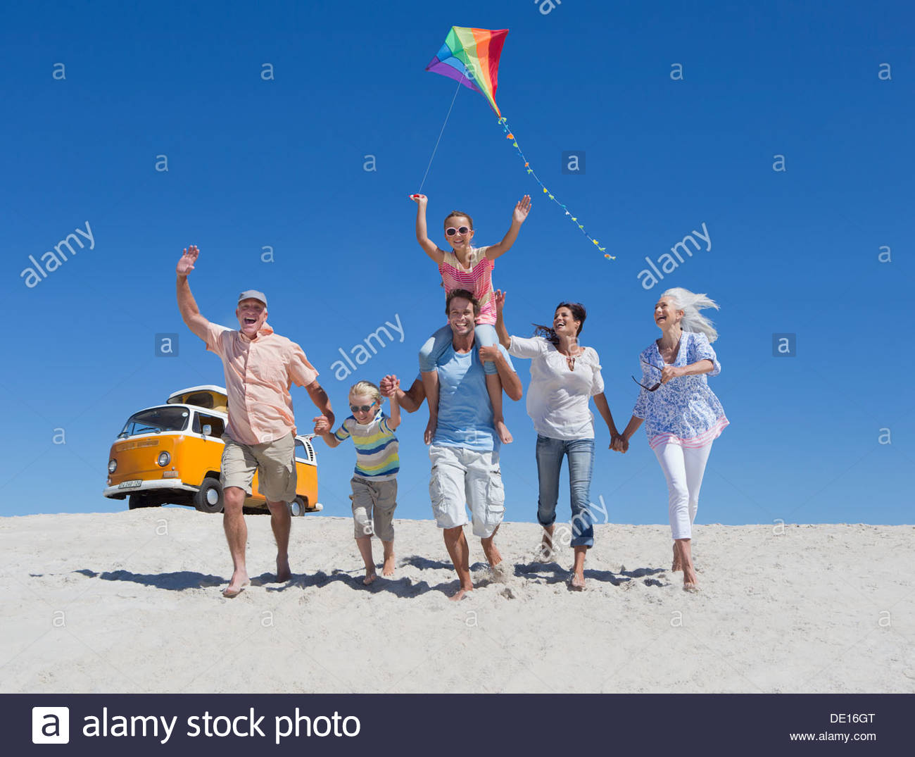 Happy multi-generation family with kite running and waving on sunny beach with van in background - Stock Image