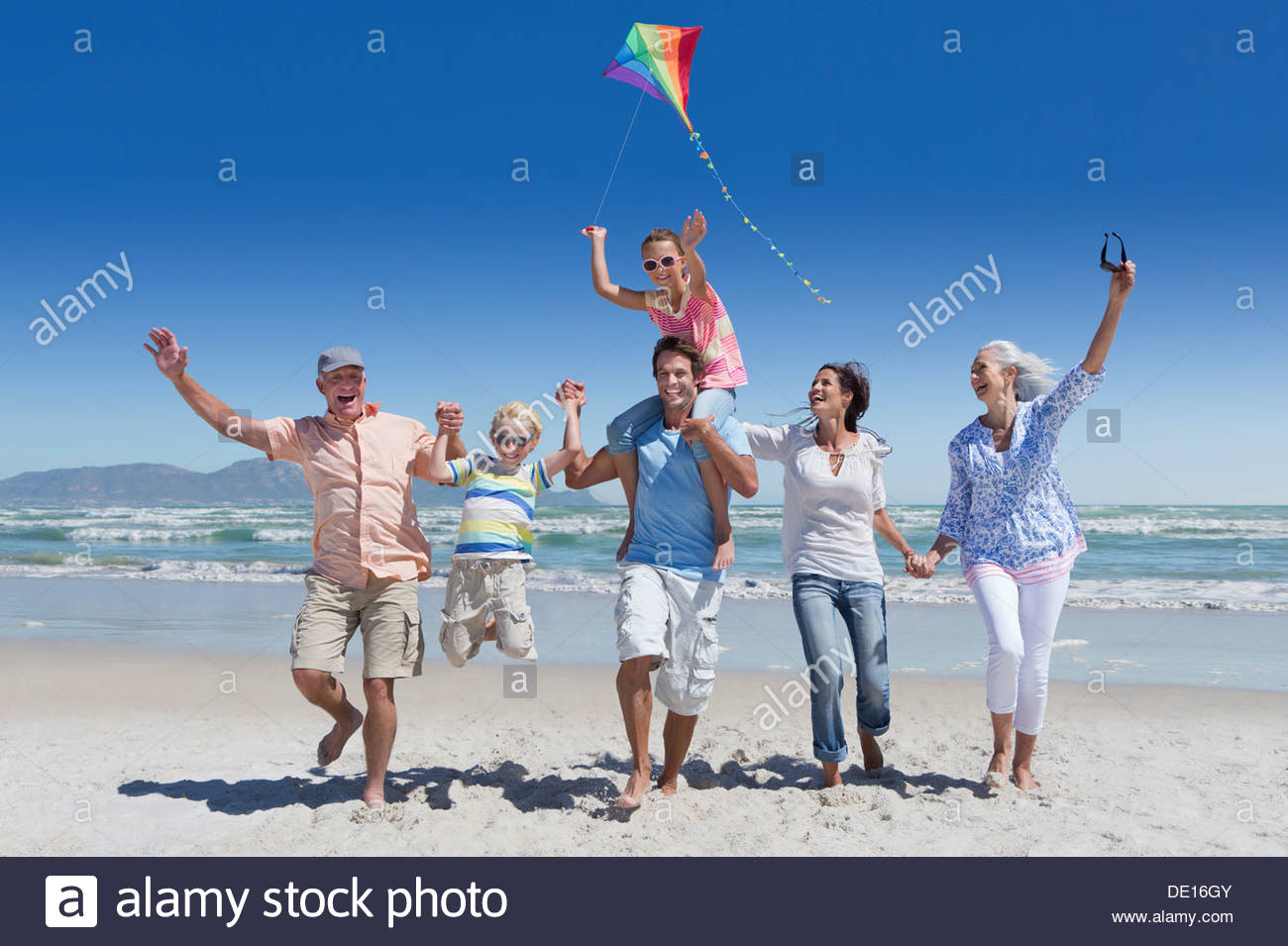 Happy multi-generation family with kite running and waving on sunny beach - Stock Image