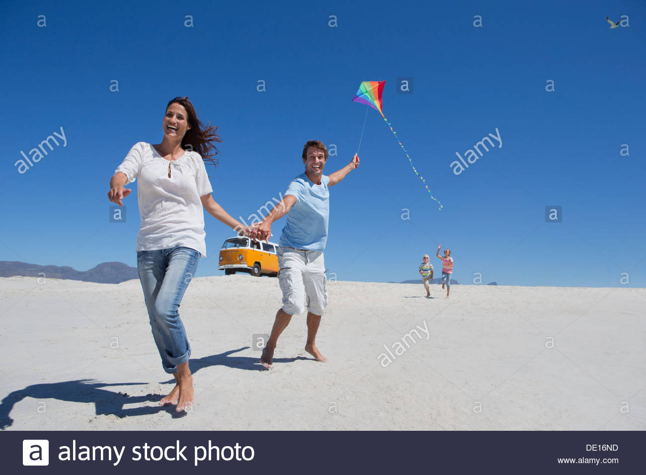 Happy family with kite running on sunny beach with van in background - Stock Image