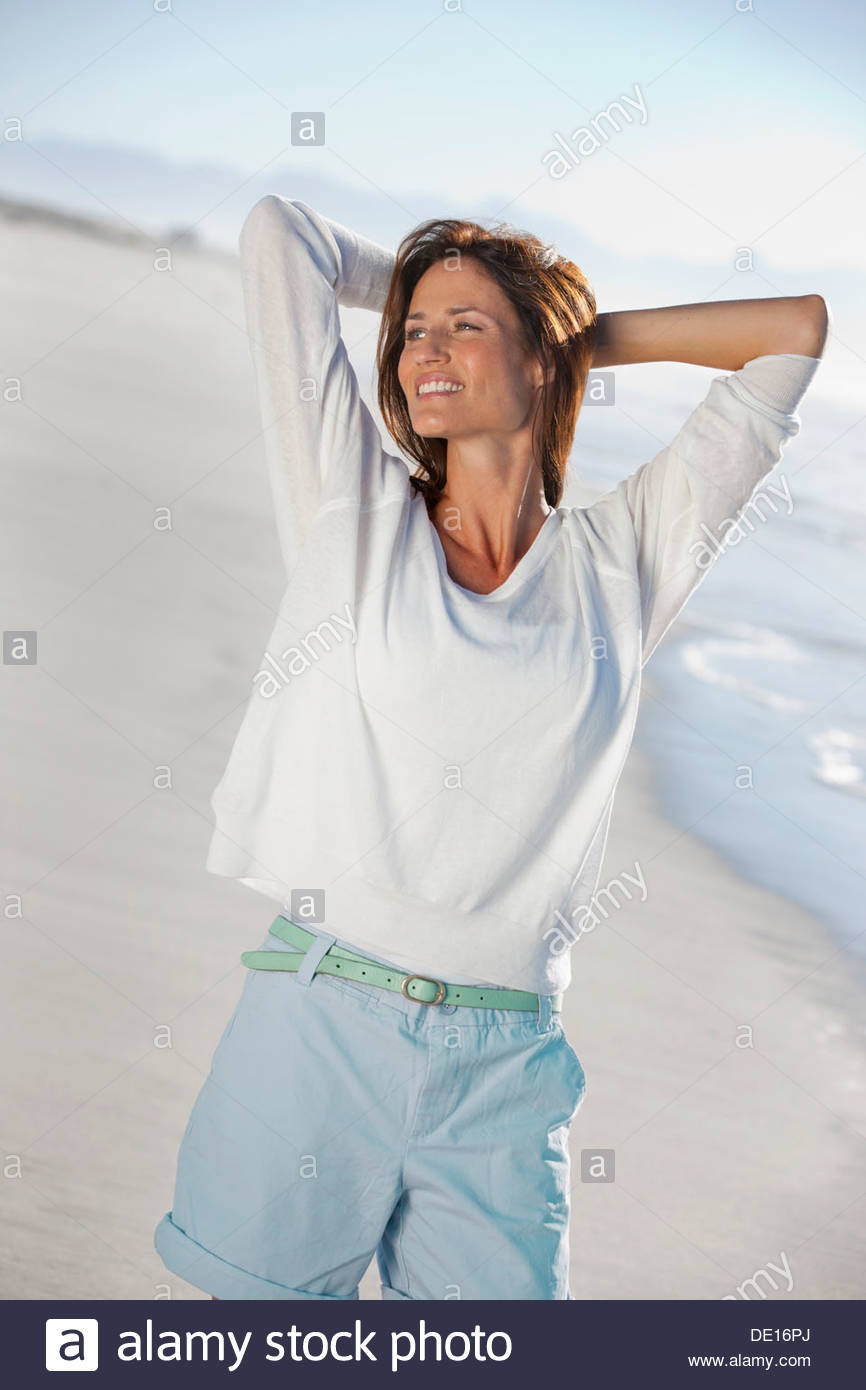 Happy woman with hands behind head on sunny beach - Stock Image