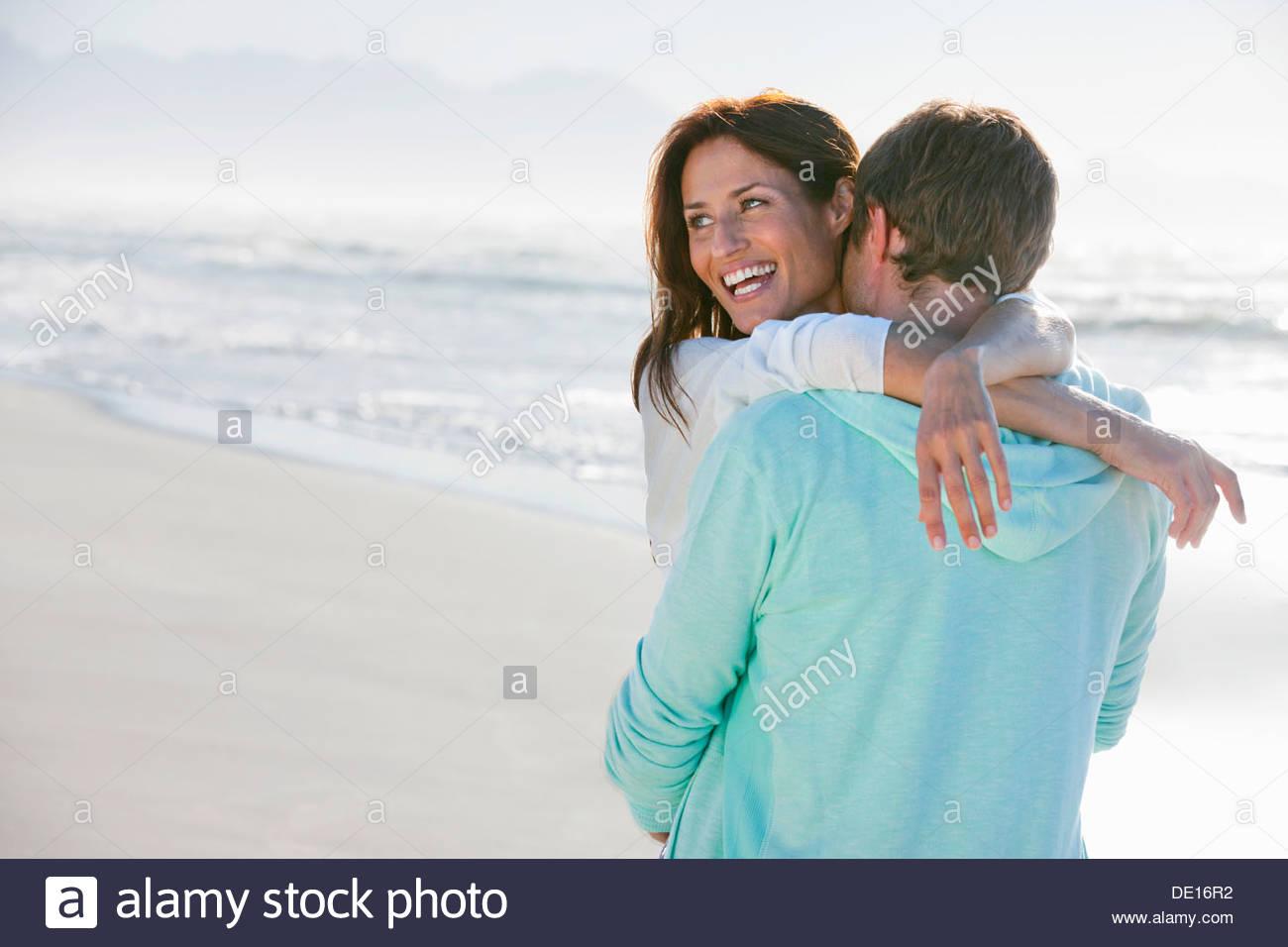 Happy couple hugging on sunny beach - Stock Image