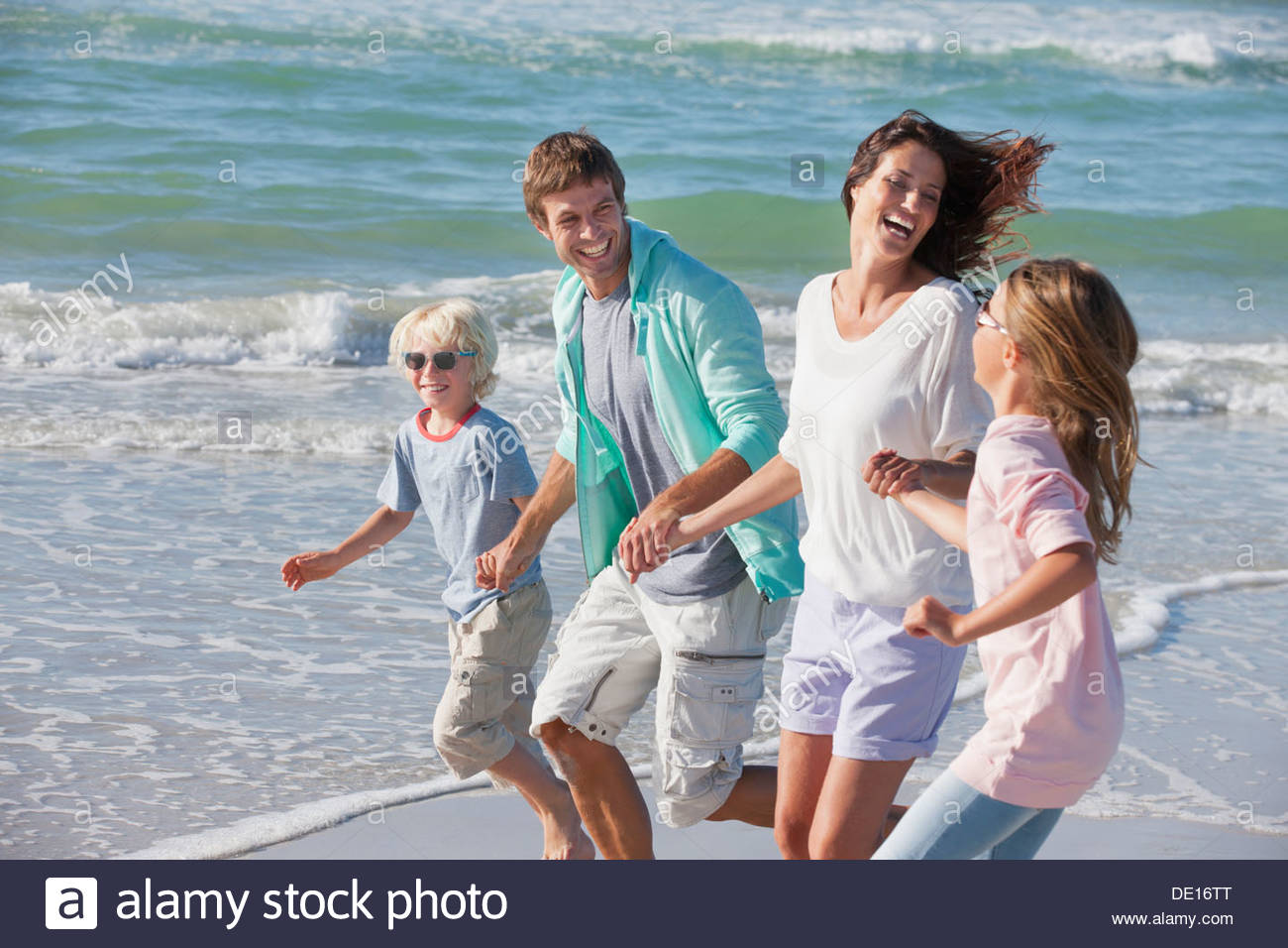 Happy family holding hands running on sunny beach Stock Photo