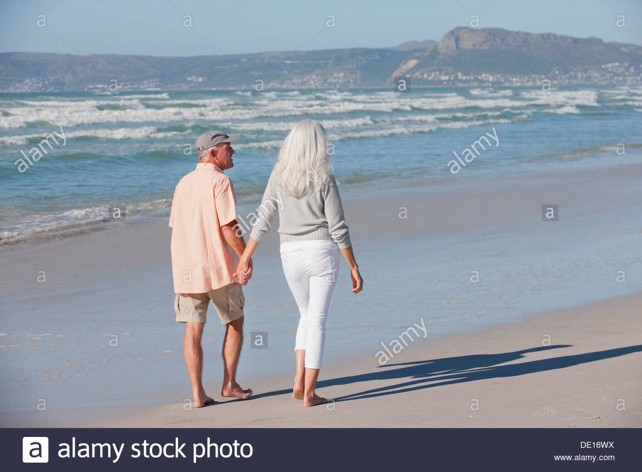 Senior couple holding hands and walking on sunny beach Stock Photo