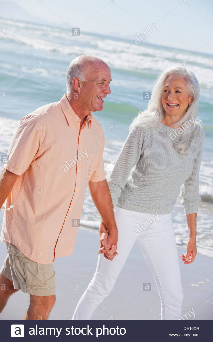 Happy senior couple holding hands and walking on sunny beach - Stock Image