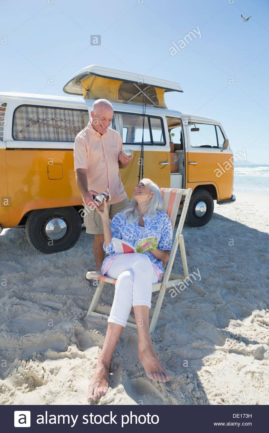 Senior couple drinking coffee on beach outside van - Stock Image