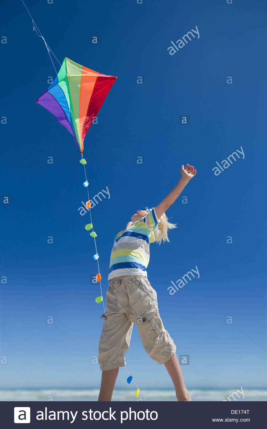 Boy reaching for multicolor kite in blue sky - Stock Image