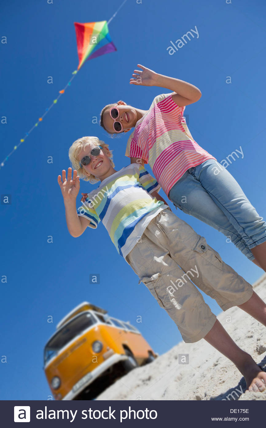 Portrait of happy brother and sister waving under kite with van in background - Stock Image