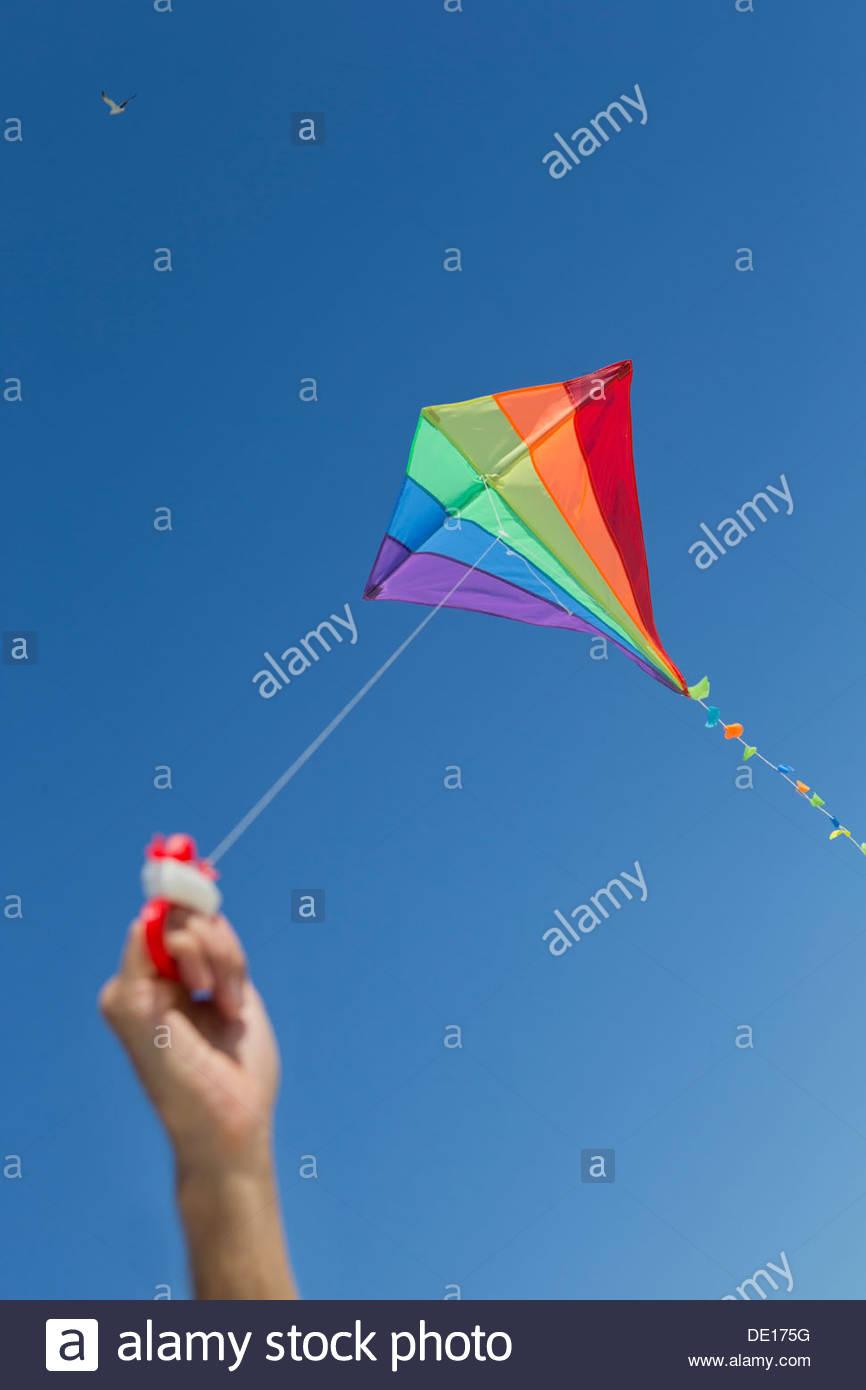 Boy flying multicolor kite in blue sky - Stock Image