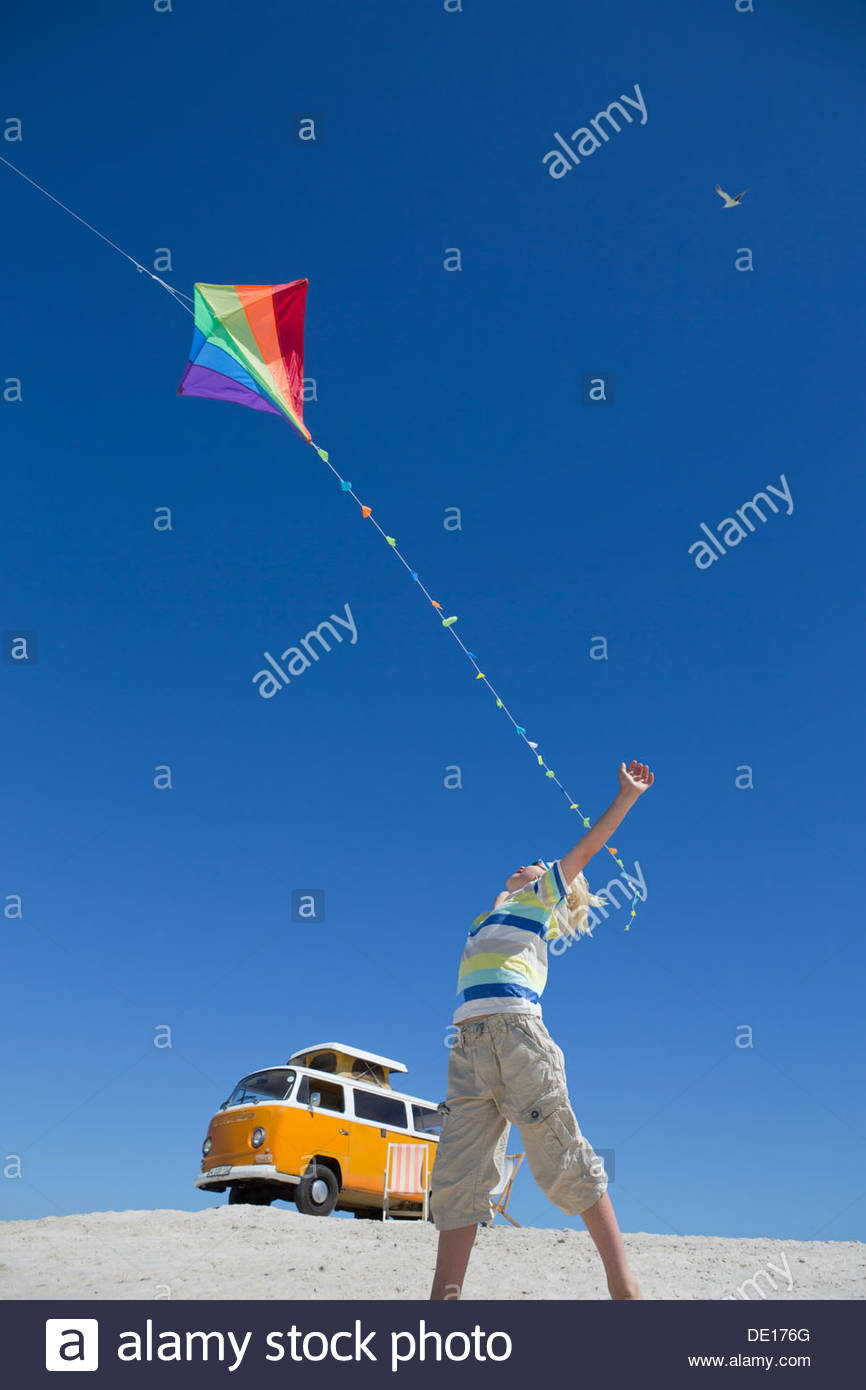 Boy flying kite on sunny beach with van in background - Stock Image