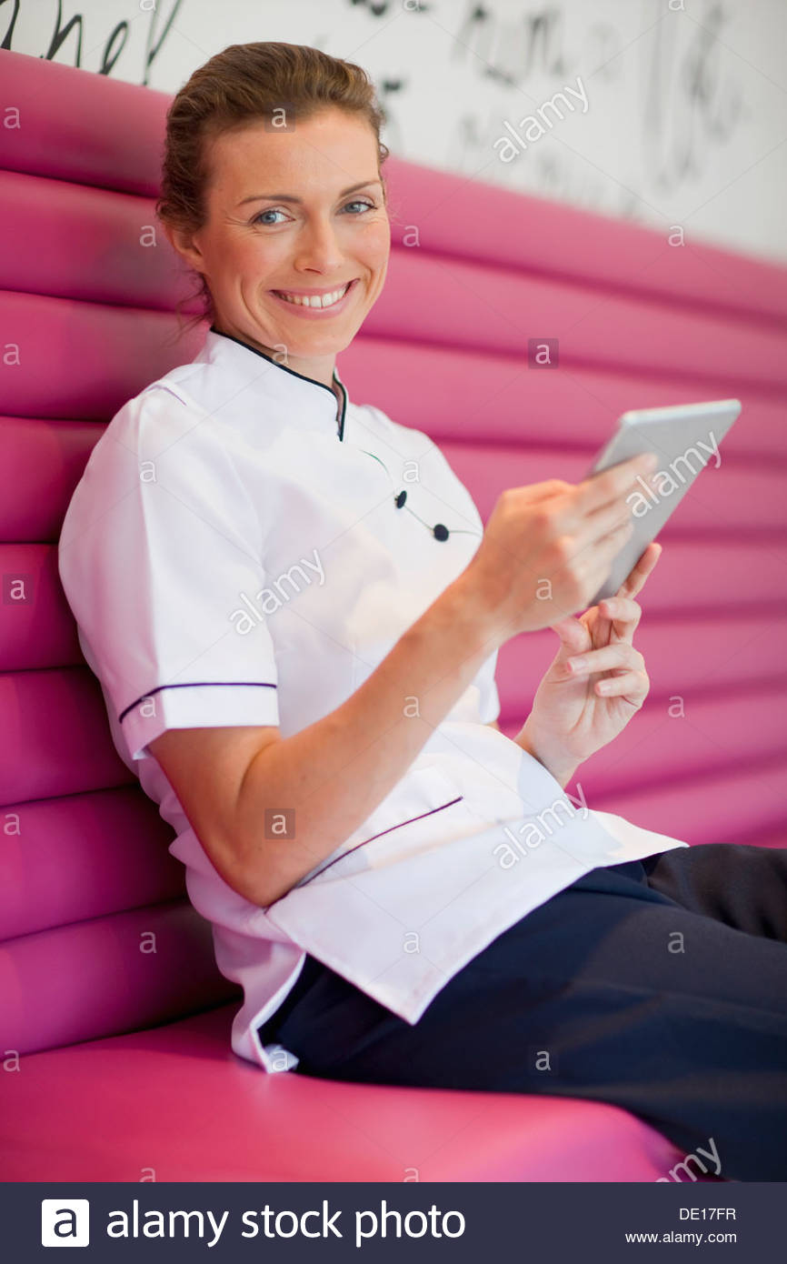 Portrait of smiling beautician with digital tablet taking a break in salon - Stock Image