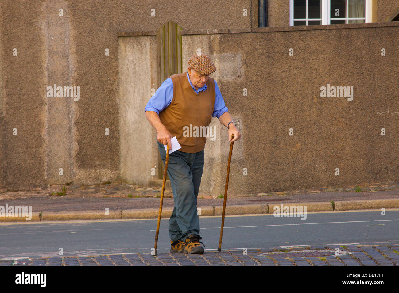 Old man with walking sticks, crossing the road to post a letter. Northern England. - Stock Image