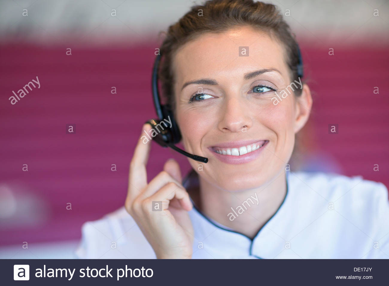 Close up of smiling beautician talking on the phone with headset - Stock Image