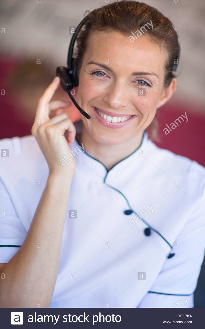 Close up portrait of smiling beautician talking on the phone with headset - Stock Image
