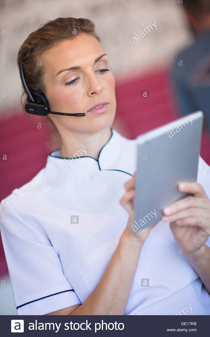 Beautician with digital tablet talking on the phone with headset - Stock Image