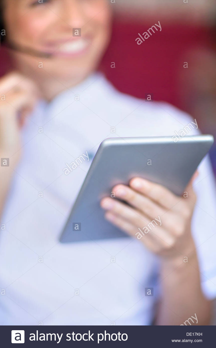 Close up of smiling beautician with digital tablet talking on the phone with headset - Stock Image