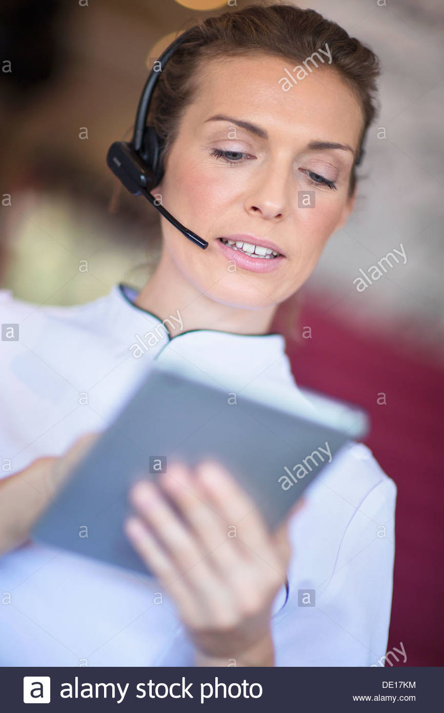 Close up of beautician with digital tablet talking on the phone with headset - Stock Image