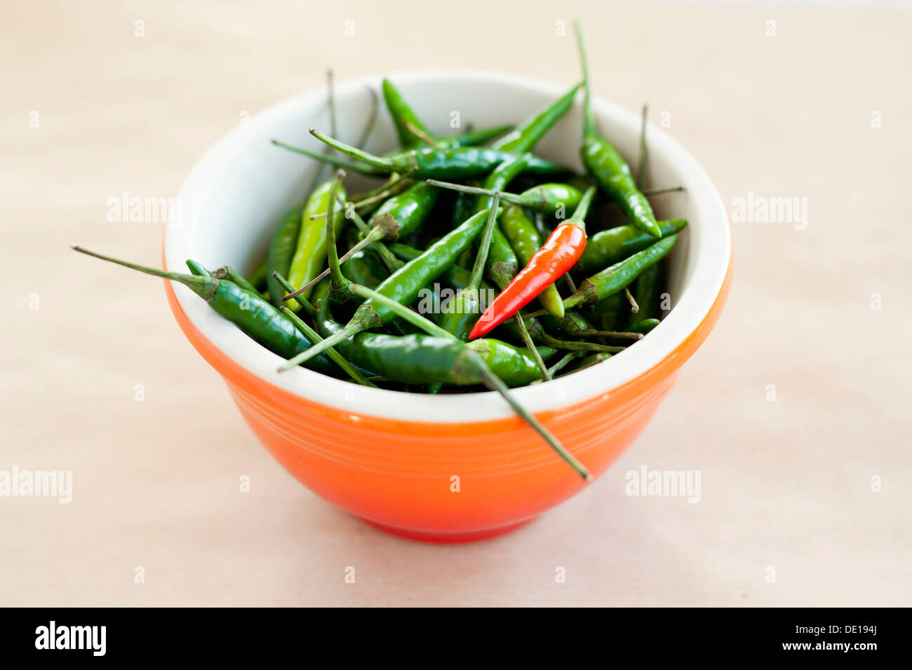 Bowl of Bird's eye chili peppers, green and red chillies, orange bowl. Neutral background. - Stock Image