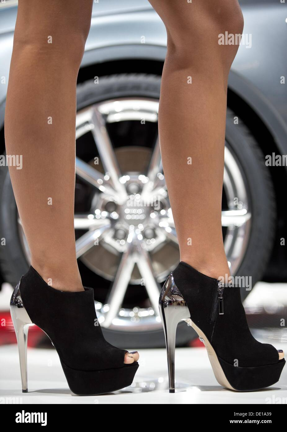 1a9eefb16c8 A hostess wearing chrome-plated high heels stands in front of an alloy  wheel at