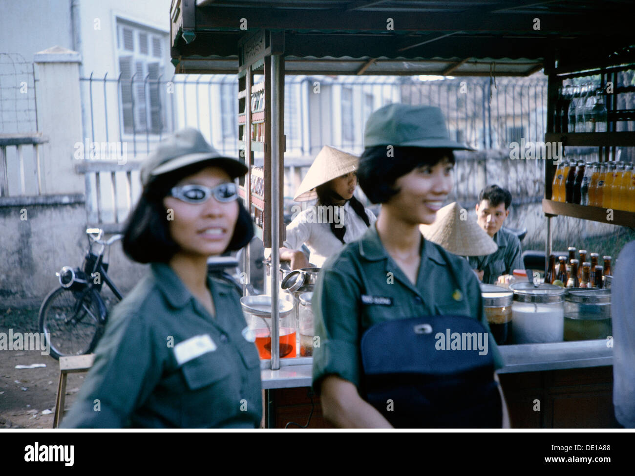 Vietnam War 1957 - 1975, Vietnamese servicewoman of the Women's Corps of the Army of the Republic of Vietnam at a berverage booth, South Vietnam, 1965, ARVN, military, Armed Forces, uniform, uniforms, beverages, beverage, booth, trade, South-East Asia, South East Asia, Southeast Asia, Far East, Viet Nam conflict, Viet Nam, Vietnam, war, wars, conflict, conflicts, 1960s, 60s, 20th century, people, group, groups, women, servicewoman, female soldier, servicewomen, female soldiers, historic, historical, Additional-Rights-Clearences-NA - Stock Image