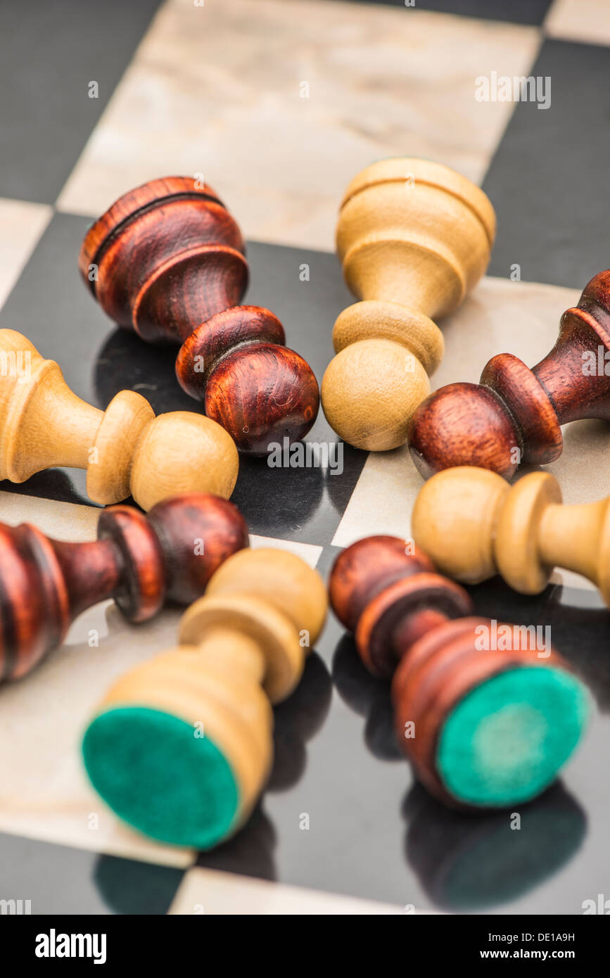 Closeup of chess pieces, white and black pawns lying on chessboard representing teamwork. - Stock Image