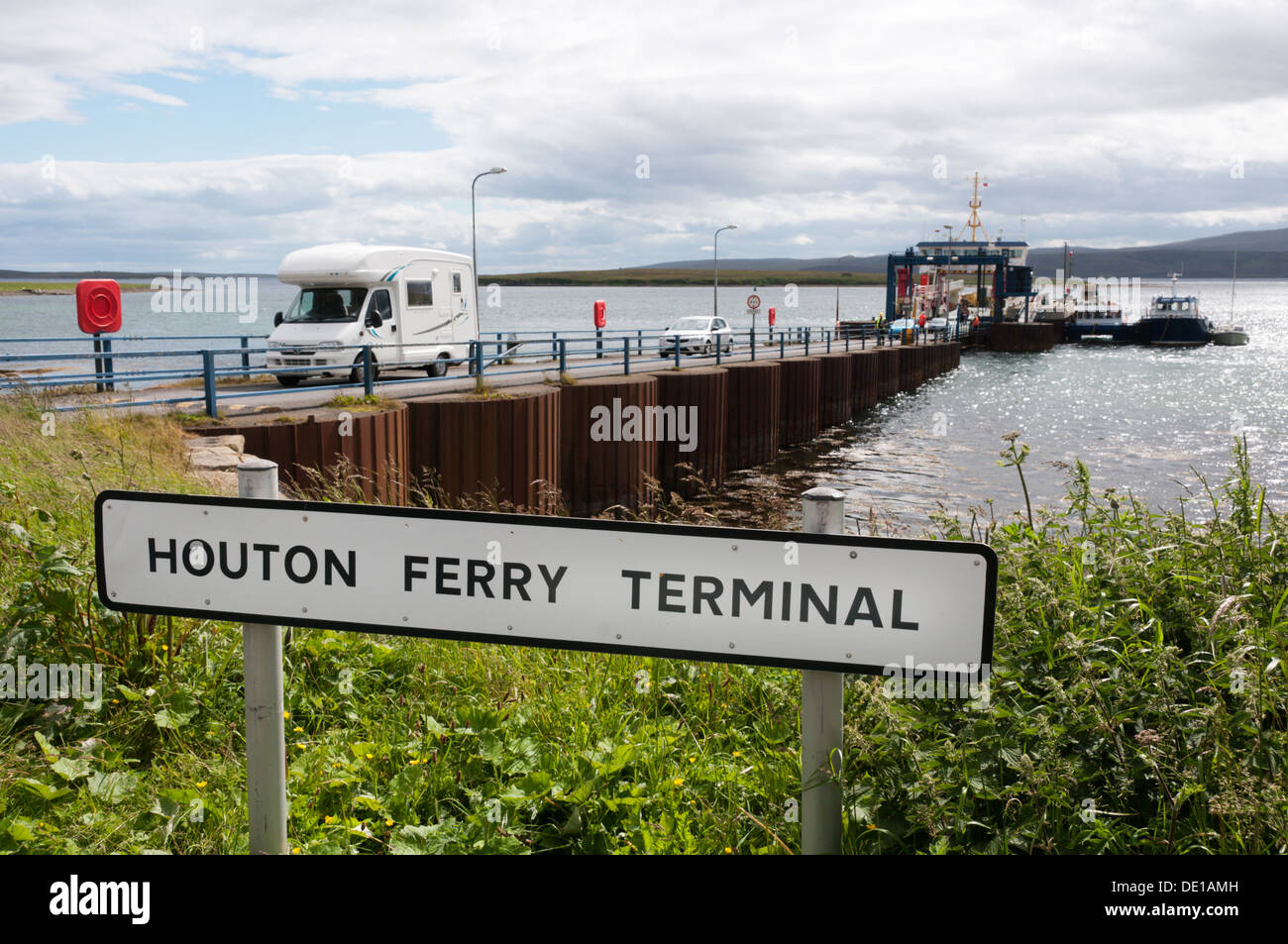 Sign for Houton Ferry Terminal on Orkney Mainland with vehicles, including a camper van, leaving ferry in background. Stock Photo