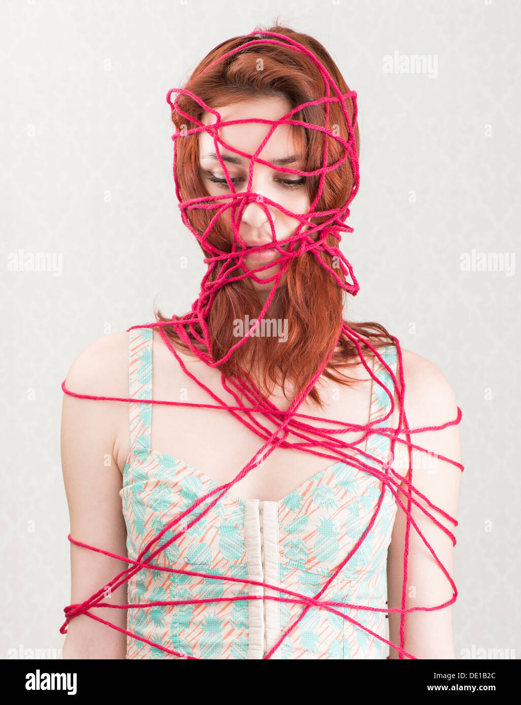 Conceptual image of woman trapped and constrained with red cotton yarn - Stock Image