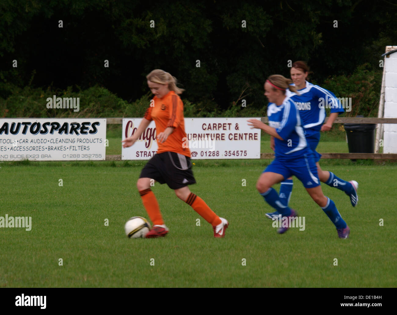 Fast paced action during women's football match, Bude, Cornwall, UK 2013 - Stock Image