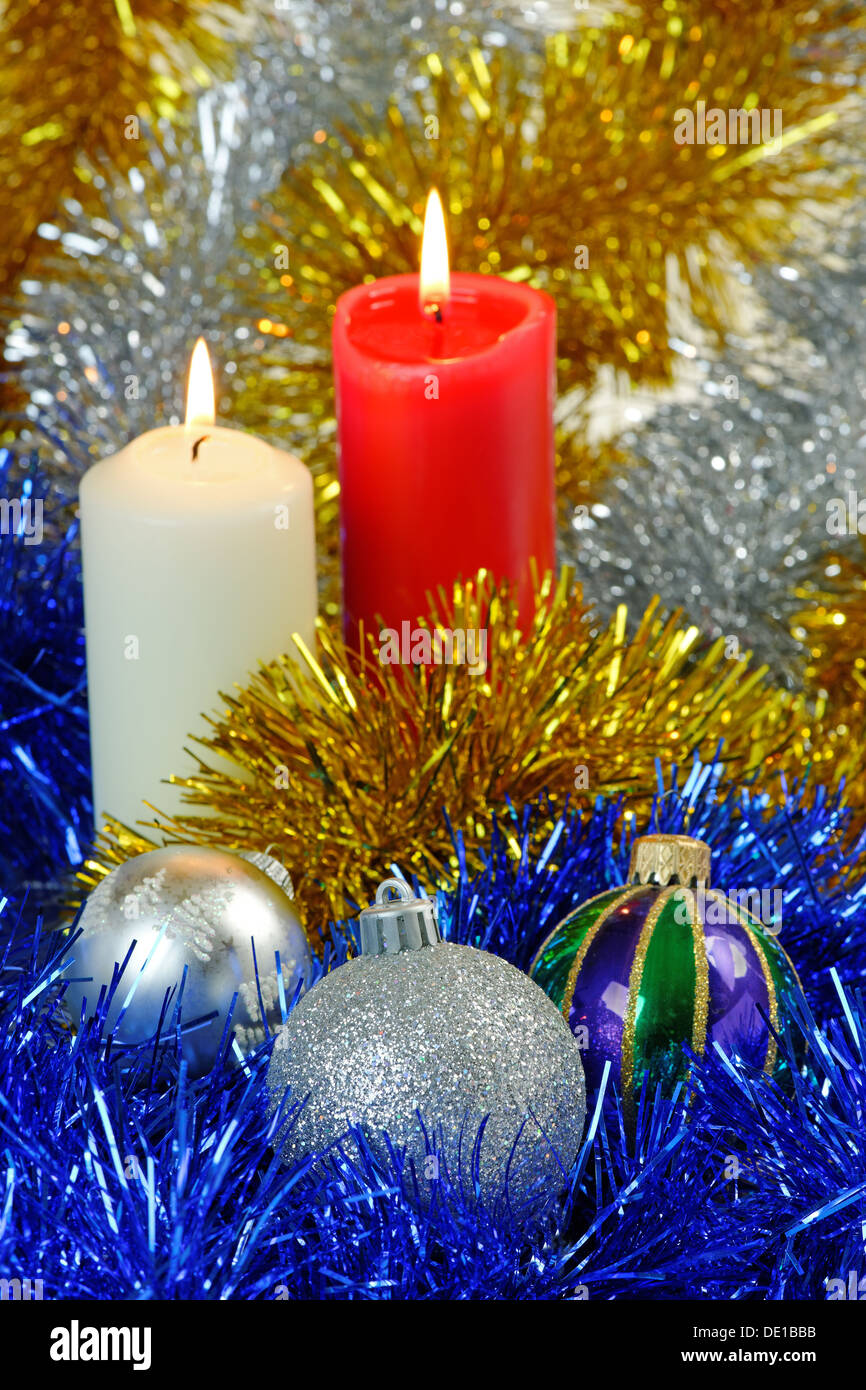 Christmas baubles and candles against a twinkling tinsel background - Stock Image
