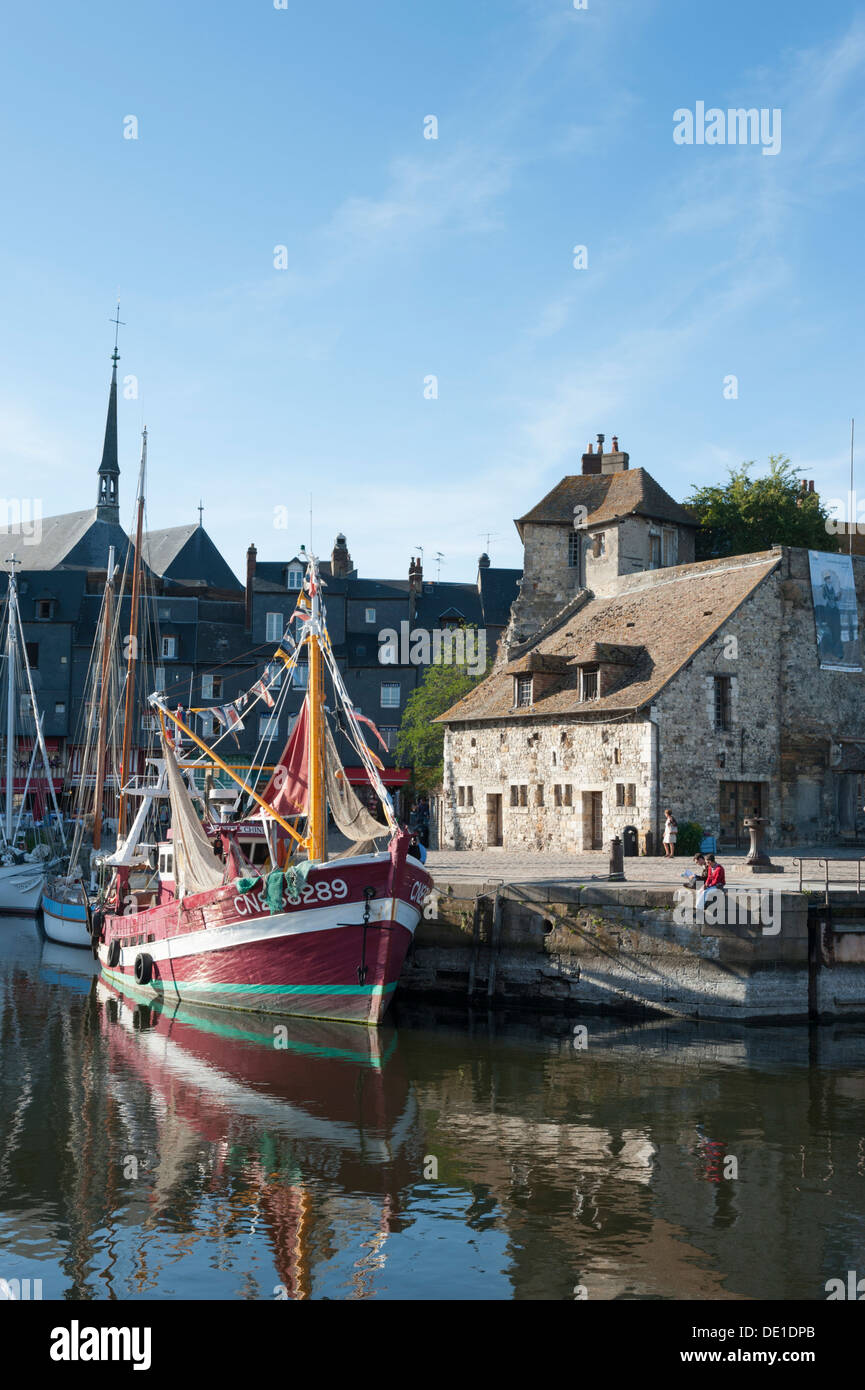 The harbour and port at Honfleur Normandy France with fishing boats moored and old buildings on the quay. - Stock Image