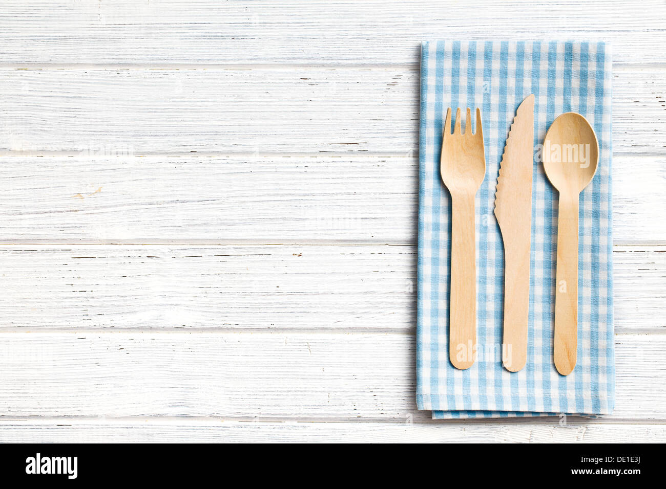set of wooden cutlery and checkered napkin - Stock Image