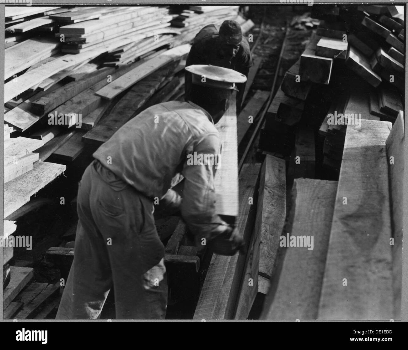 Charles County, Maryland. Two Negro workers pile the sawed planks at the sawmill in the Nanjemoy com . . . 521564 - Stock Image
