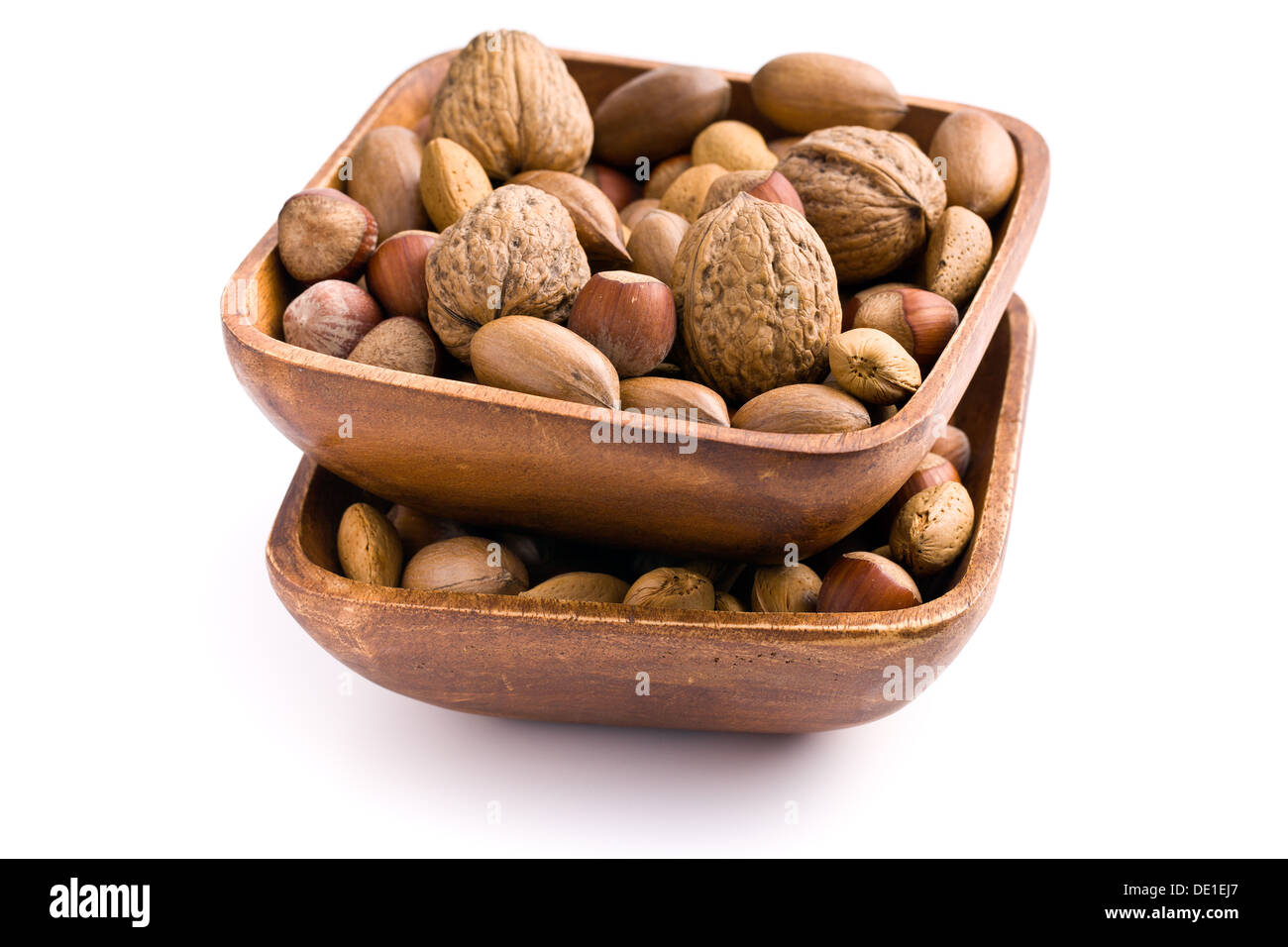 various unpeeled nuts in wooden bowl on white background - Stock Image