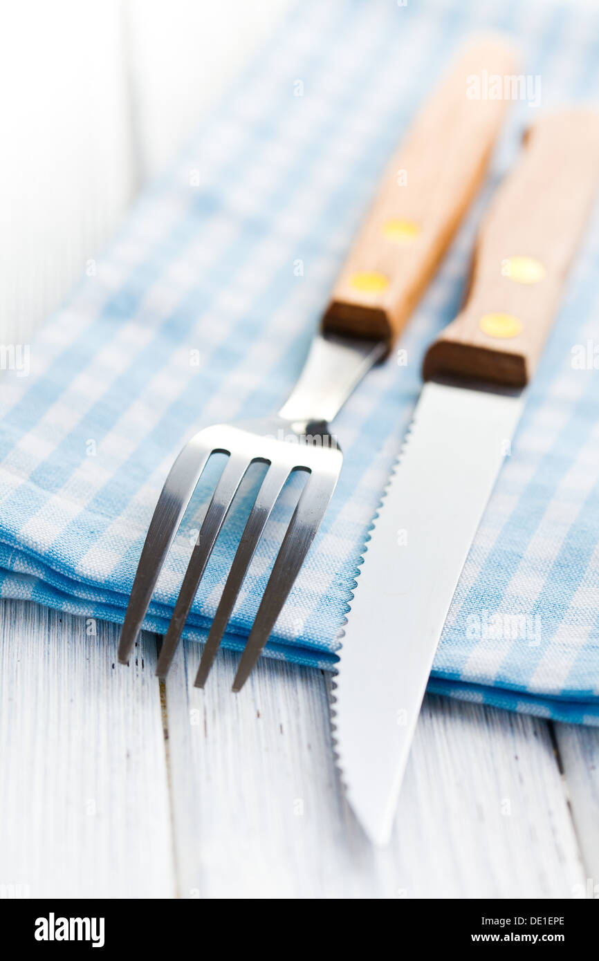 the knife and fork on checkered napkin - Stock Image