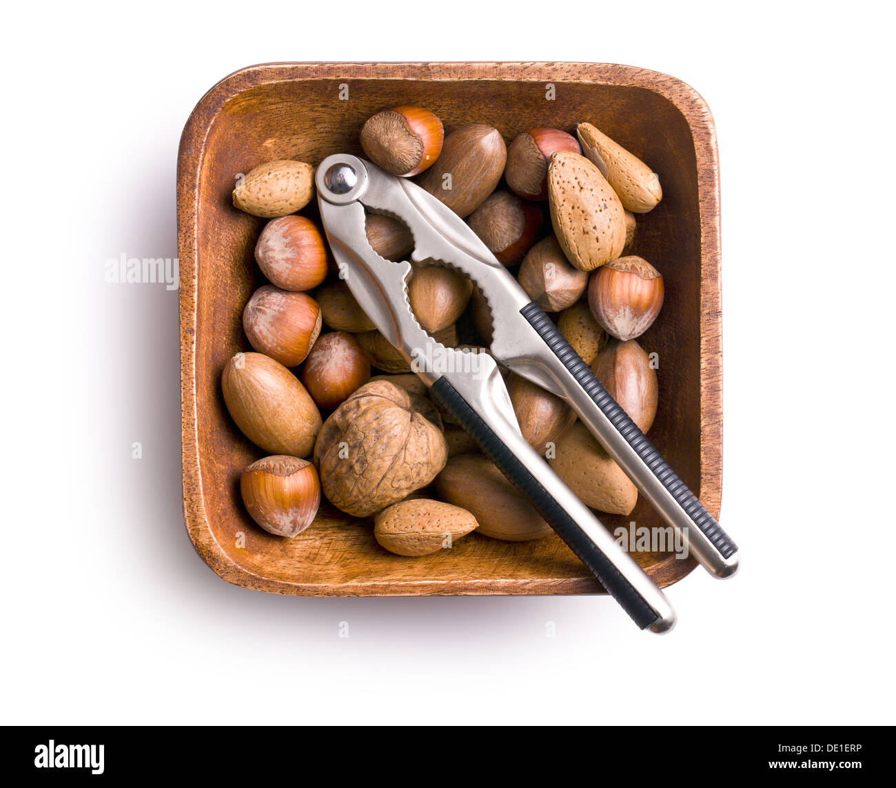 various unpeeled nuts in wooden bowl - Stock Image