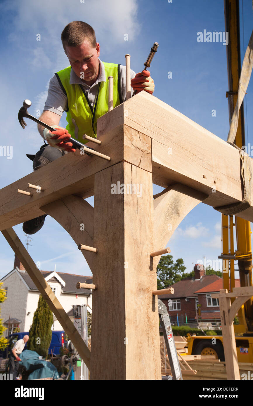 self building house, constructing green oak timber framed garage, pegging frame, whist crane lifts heavy structure - Stock Image