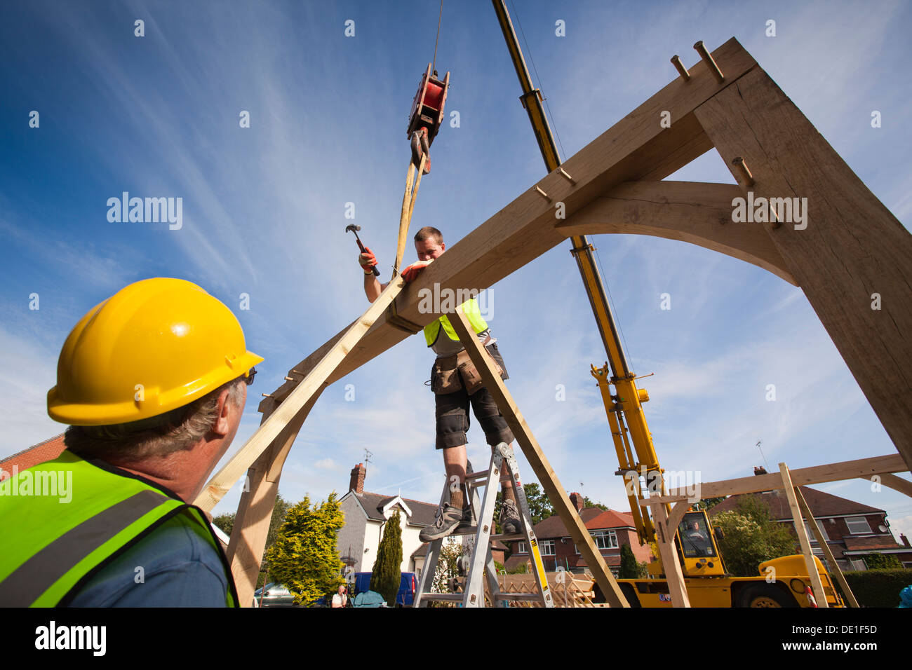 self building house, constructing green oak timber framed structure, using hired crane to lift heavy wooden frame - Stock Image