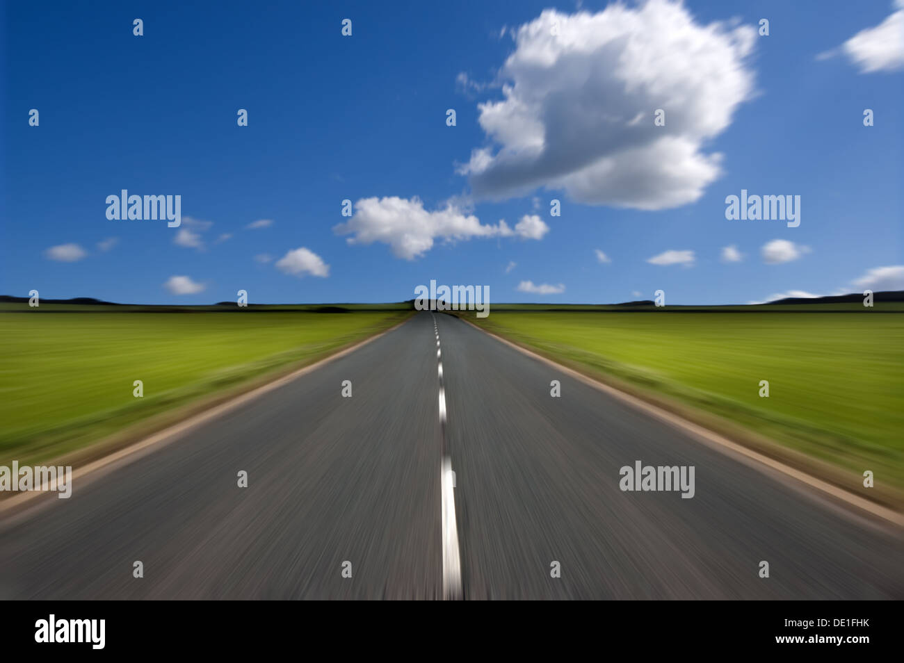 Rural road stretching out into the distance with motion blur under a big expanse of blue sky. Stock Photo