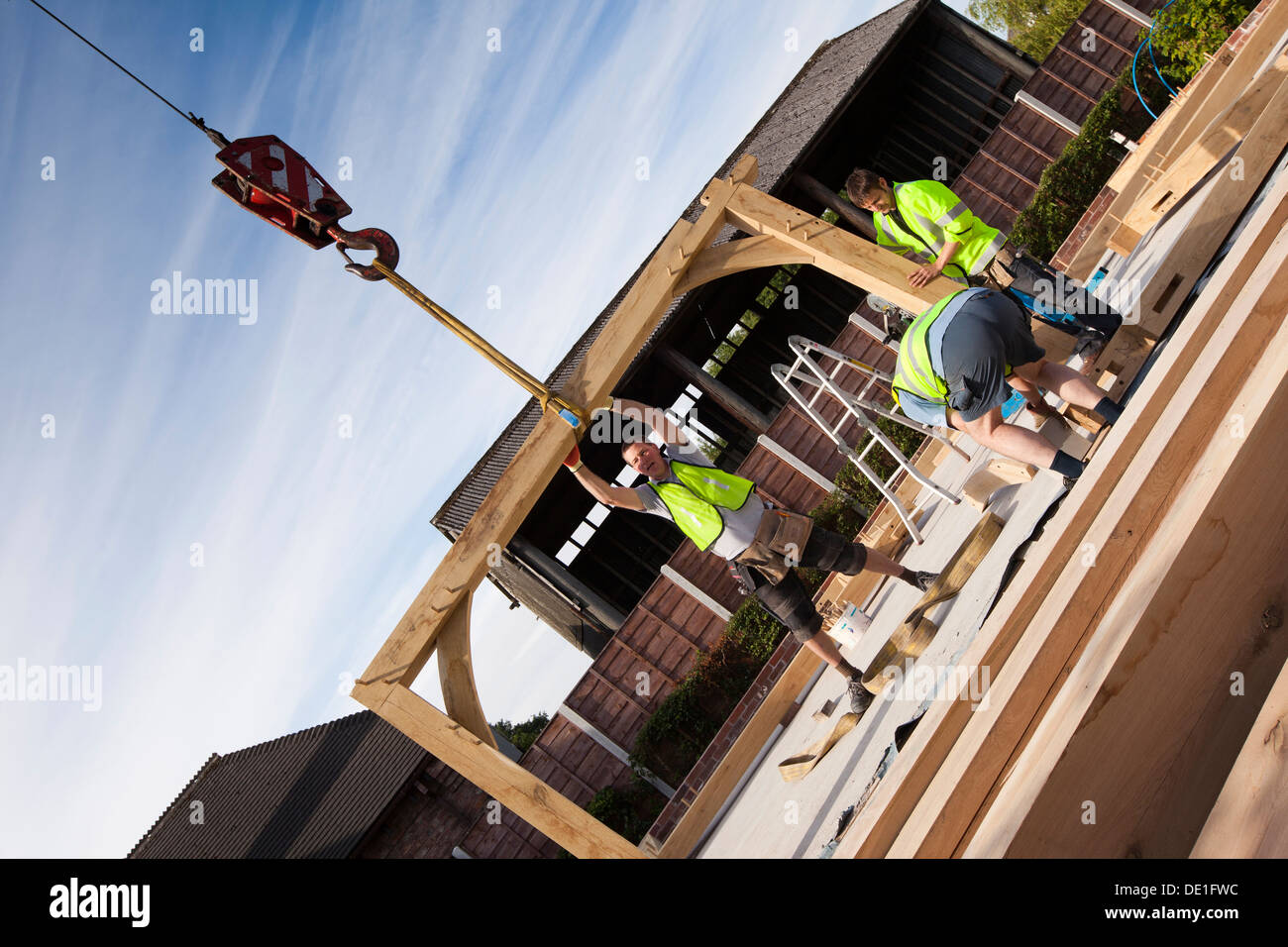 self building house, constructing green oak timber framed structure, using hired crane to lift heavy wooden components - Stock Image