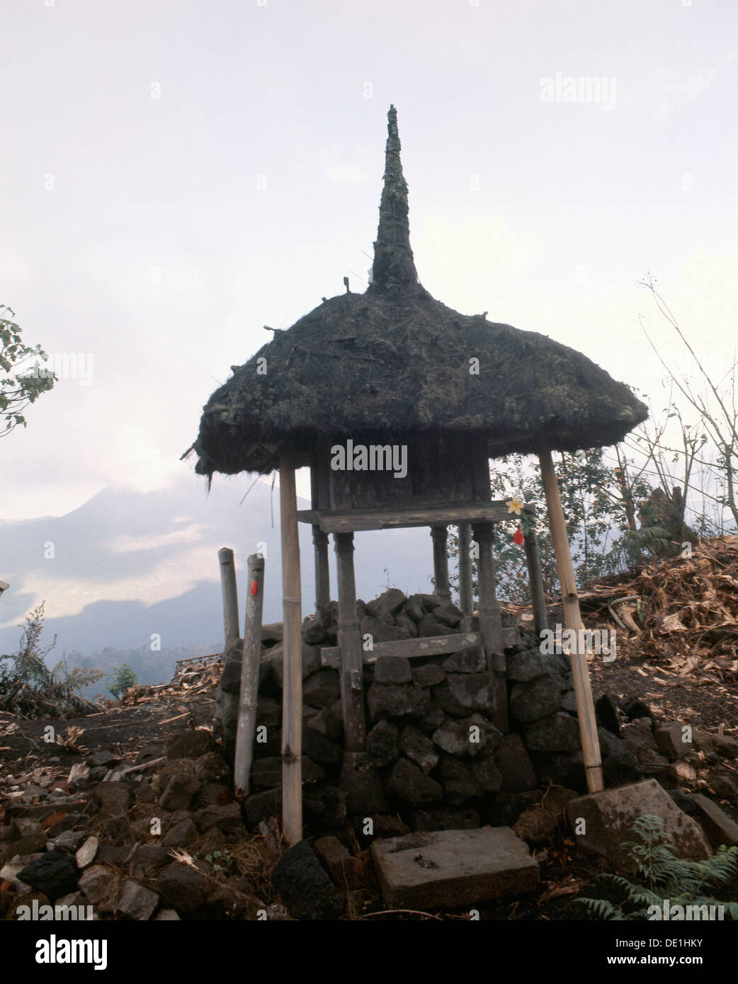 A tiny shrine, its' roof recalling the cosmic mountain, standing before the volcano Gunung Batur. - Stock Image